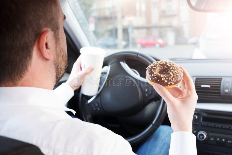 Man som har frukosten, och placerad körning i bil arkivfoto