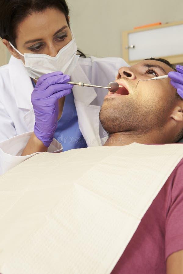 Man som har kontrollen upp på tandläkarekirurgi royaltyfri fotografi