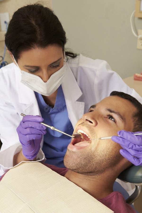Man som har kontrollen upp på tandläkarekirurgi fotografering för bildbyråer