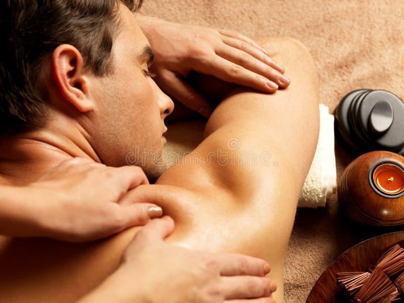 Man som har massage i brunnsortsalongen royaltyfria foton