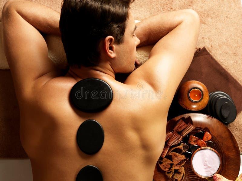 Man som har stenmassage i brunnsortsalong arkivfoto