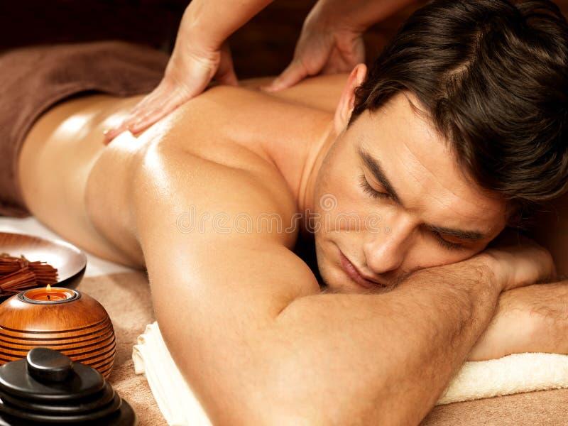Man som har tillbaka massage i brunnsortsalongen royaltyfri bild