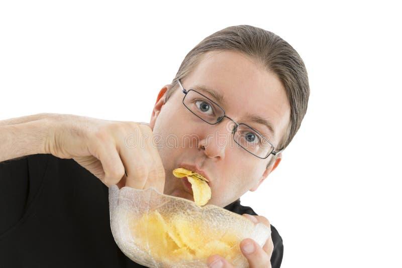 Man som hastigt äter potatischiper royaltyfri fotografi