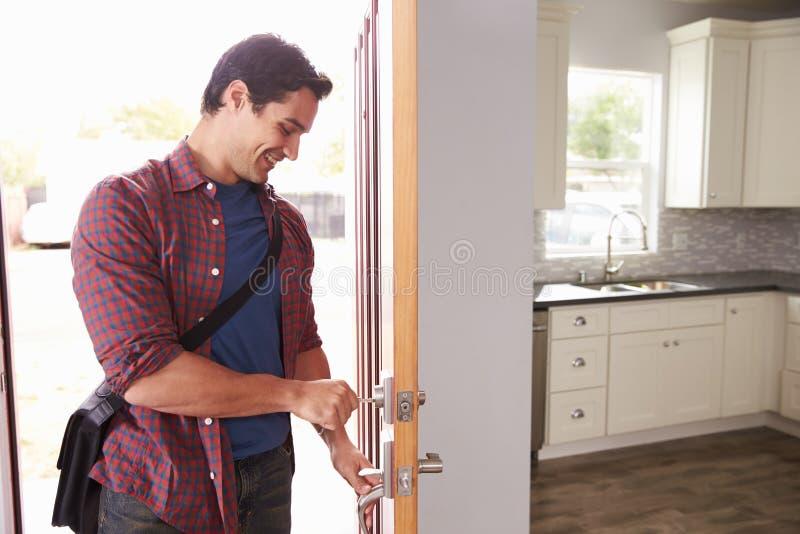 Man som hem kommer från arbets- och öppningsdörr av lägenheten arkivbild