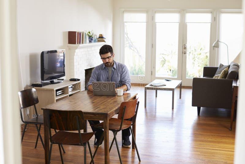 Man som hemifrån arbetar genom att använda bärbara datorn på att äta middag tabellen royaltyfria foton