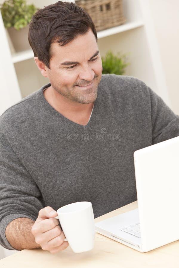 Man som hemma använder bärbar datordatoren fotografering för bildbyråer