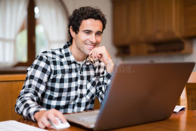 Man som hemma använder hans bärbar dator arkivbild