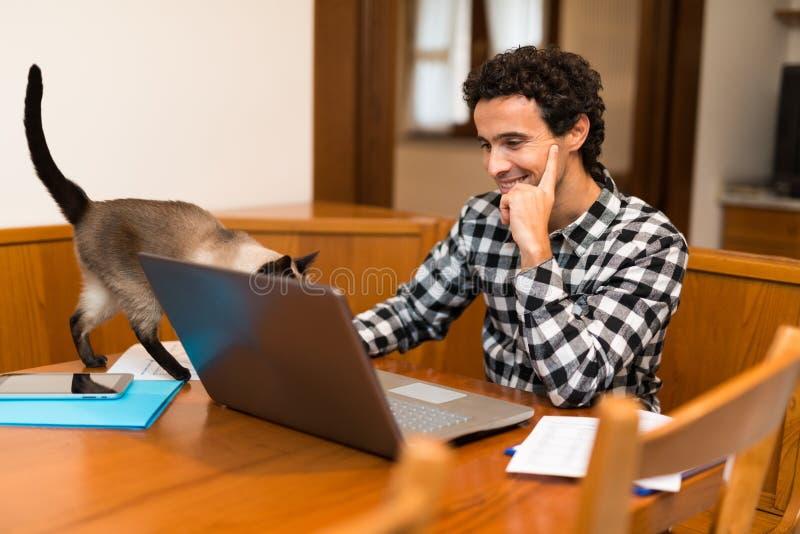 Man som hemma arbetar med hans bärbar dator royaltyfri bild