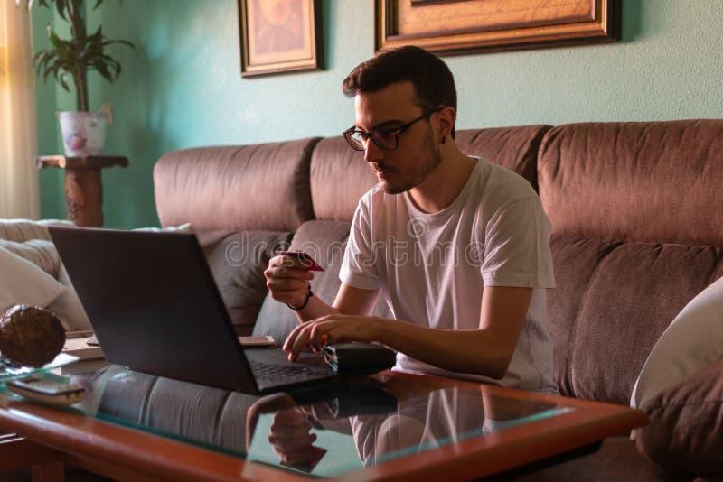 Man som hemma betalar med kreditkorten på bärbara datorn arkivfoto