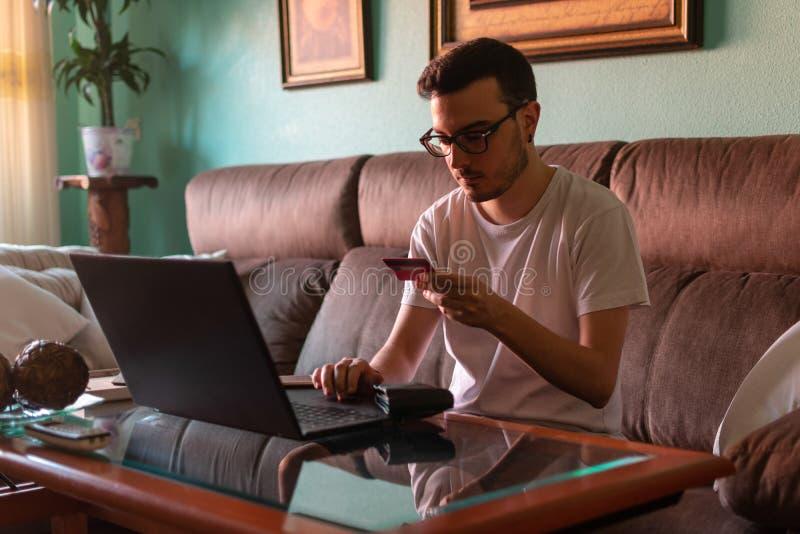 Man som hemma betalar med kreditkorten på bärbara datorn royaltyfria foton