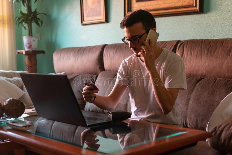 Man som hemma betalar med kreditkorten på bärbara datorn arkivbild