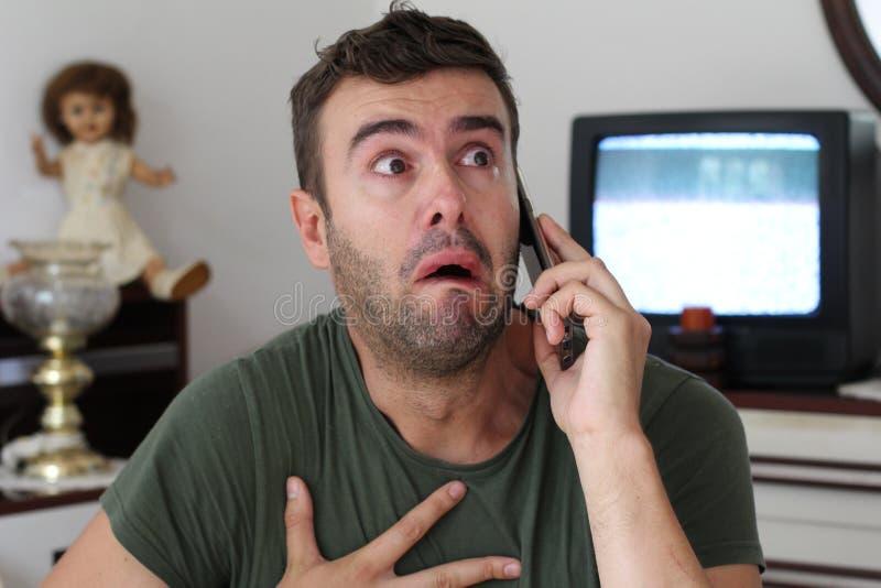 Man som hemma gråter under telefonkonversation royaltyfria bilder