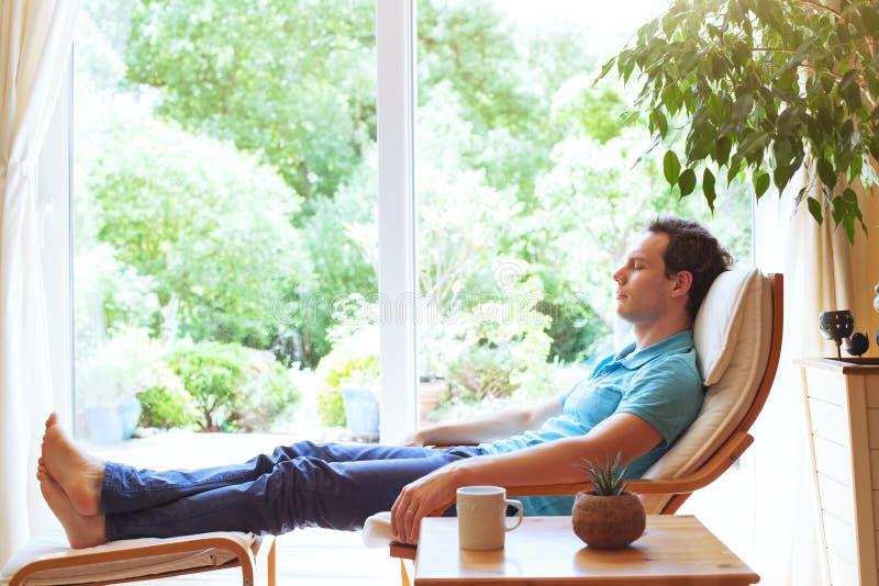Man som hemma kopplar av i solstol, avkoppling royaltyfria foton