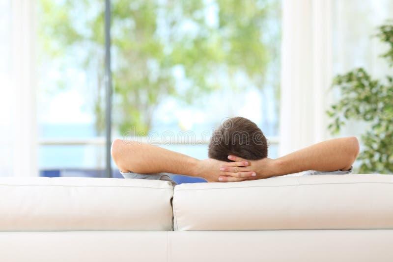 Man som hemma kopplas av på en soffa arkivbilder