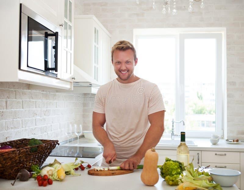 Man som hemma lagar mat att förbereda sallad i kök royaltyfri fotografi