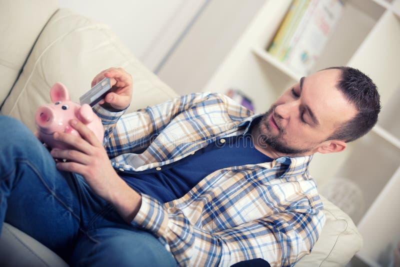 Man som hemma sätter kreditkorten i spargrisen royaltyfri bild