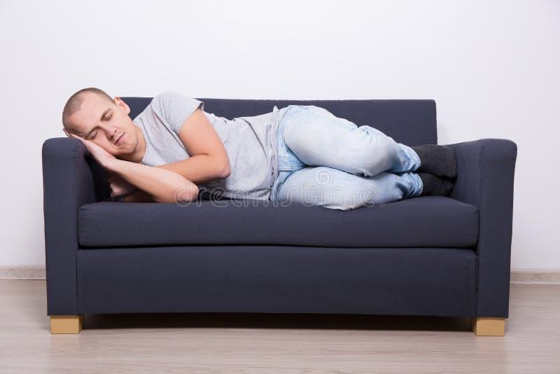 Man som hemma sover på soffan royaltyfri bild