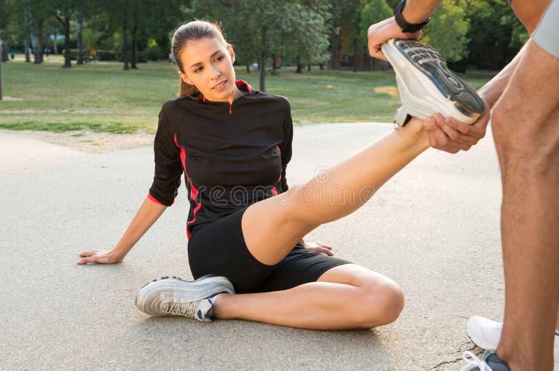 Man som hjälper den kvinnliga idrottsman nen royaltyfri fotografi