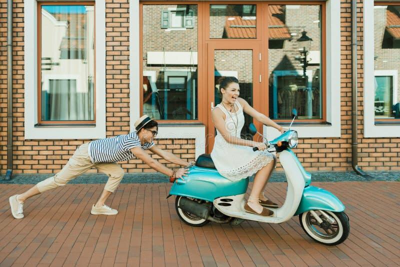 Man som hjälper den upphetsade kvinnan som rider den retro sparkcykeln royaltyfri foto