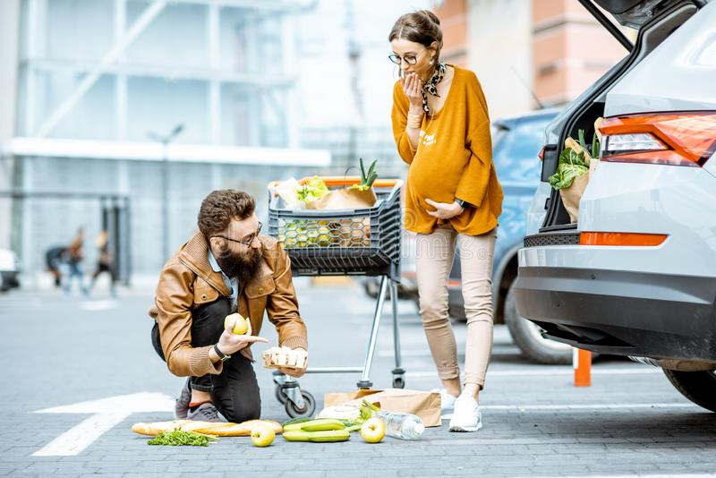 Man som hj?lper den unga gravida kvinnan n?ra supermarket arkivbild