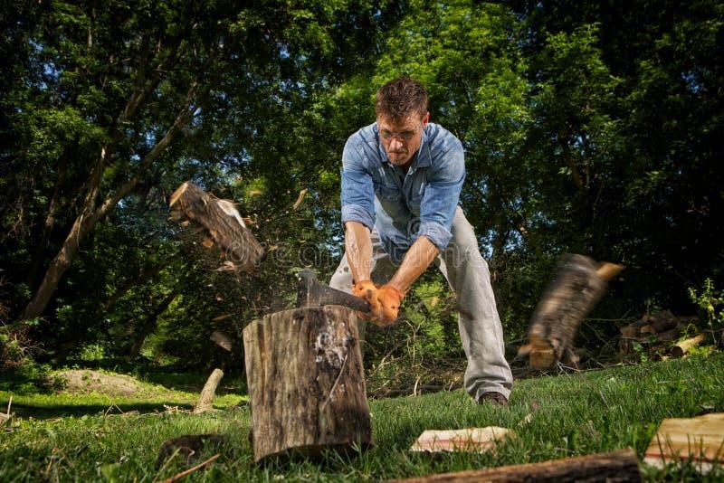 Man som hugger av trä royaltyfri bild