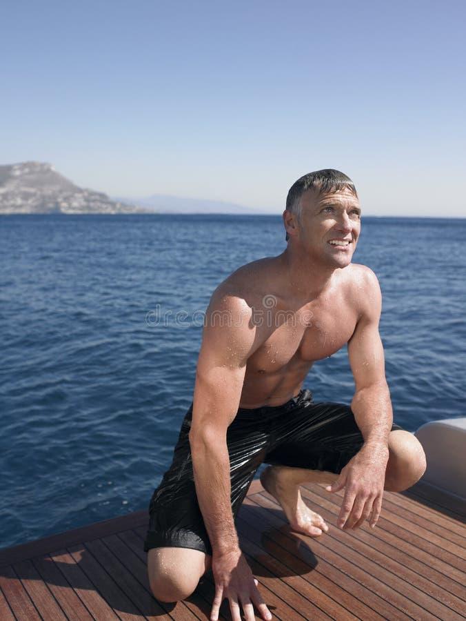 Man som huka sig ned på yachts golvtilja arkivfoto