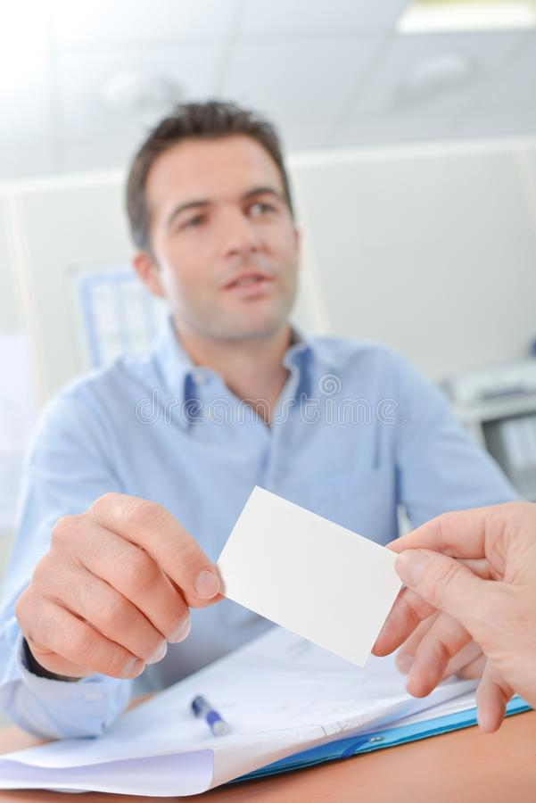Man som i regeringsställning ger kortet fotografering för bildbyråer