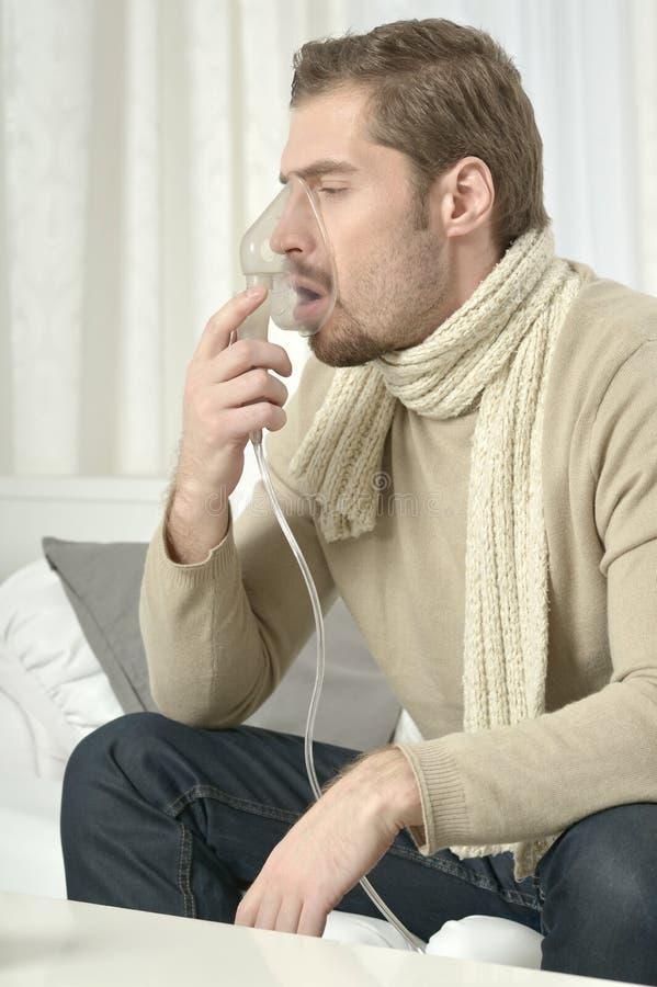 Man som inhalerar till och med inhalatormaskering arkivfoto