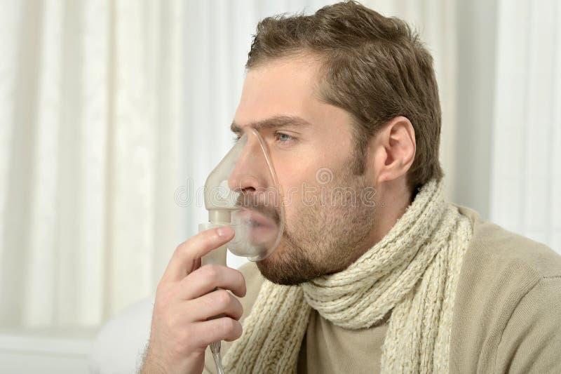 Man som inhalerar till och med inhalatormaskering arkivfoton