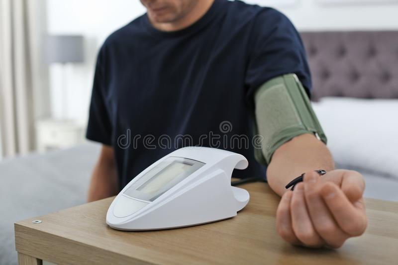 Man som inomhus kontrollerar blodtryck med sphygmomanometeren på tabellen, closeup fotografering för bildbyråer