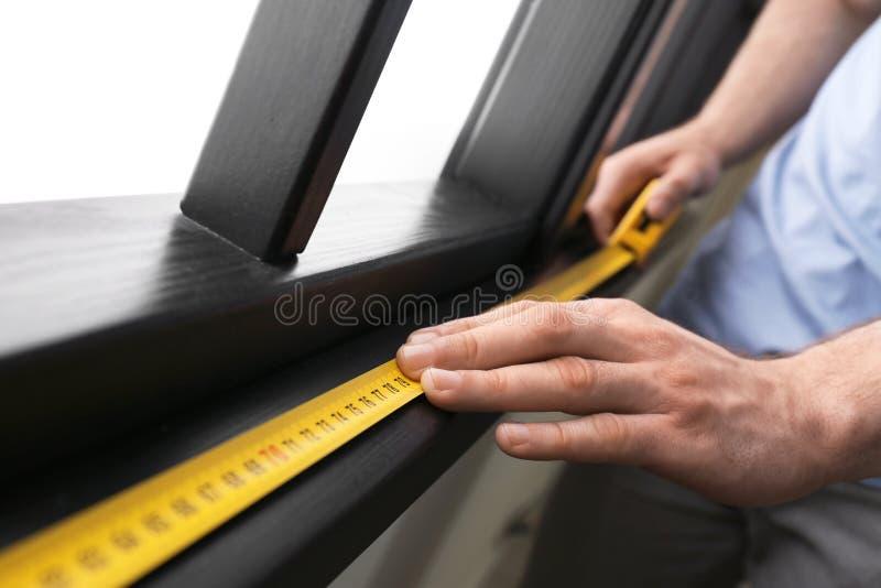 Man som inomhus mäter träfönsterramen, closeup arkivbild