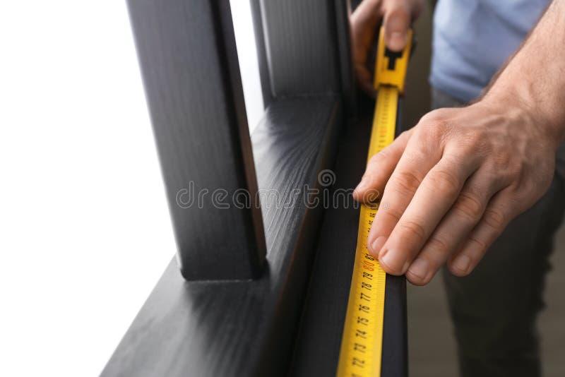 Man som inomhus mäter träfönsterramen f?r m?lningsrulle f?r konstruktion inomhus v?gg f?r hj?lpmedel arkivfoto