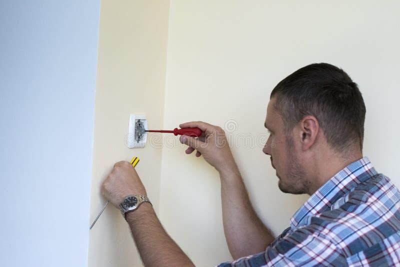 Man som installerar den ljusa strömbrytaren royaltyfria bilder