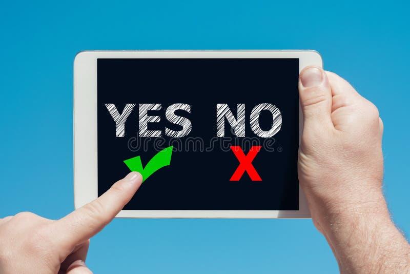 Man som ja rymmer en minnestavlaapparat med ` inga `-symboler som beslutsbegrepp och trycker på skärmen royaltyfria foton
