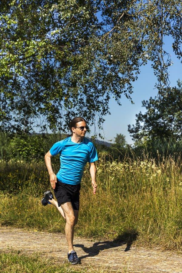 Man som joggar i natur i sommar royaltyfria foton