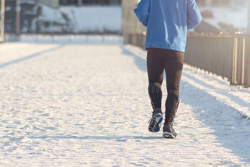 Man som joggar i vinter arkivfoto
