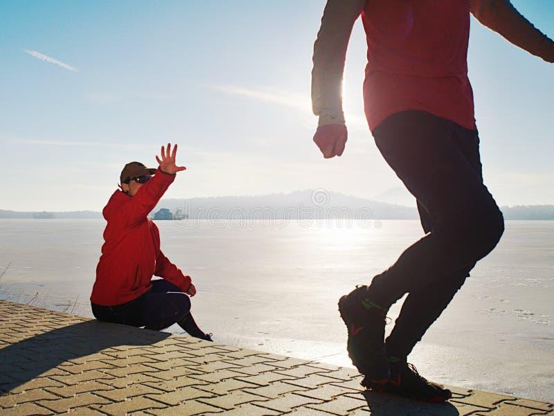 Man som joggar på hans flickvän på flodbanken Kullar med den varma solen arkivfoton