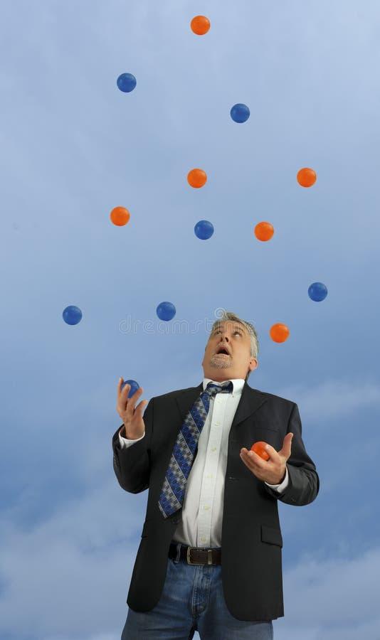 Man som jonglerar många bollar i luften som föreställer vara ut ur kontroll som är upptagen i liv och affär med flera stressig sa royaltyfria foton
