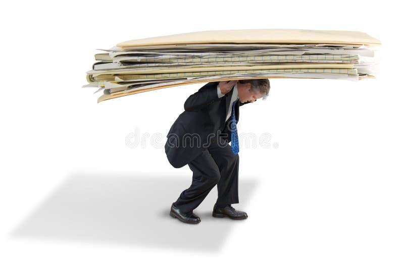 Man som kämpar under den stora högen av skrivbordsarbete royaltyfri fotografi