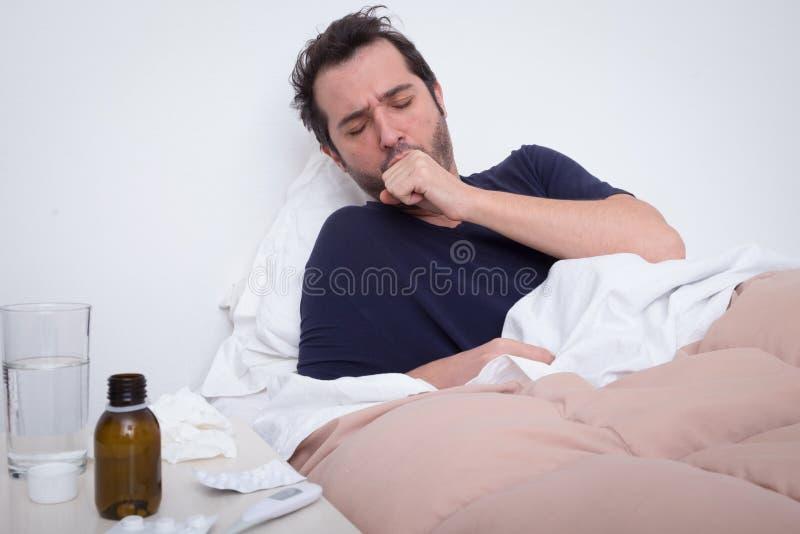 Man som känner dåligt ligga i sängen royaltyfri foto