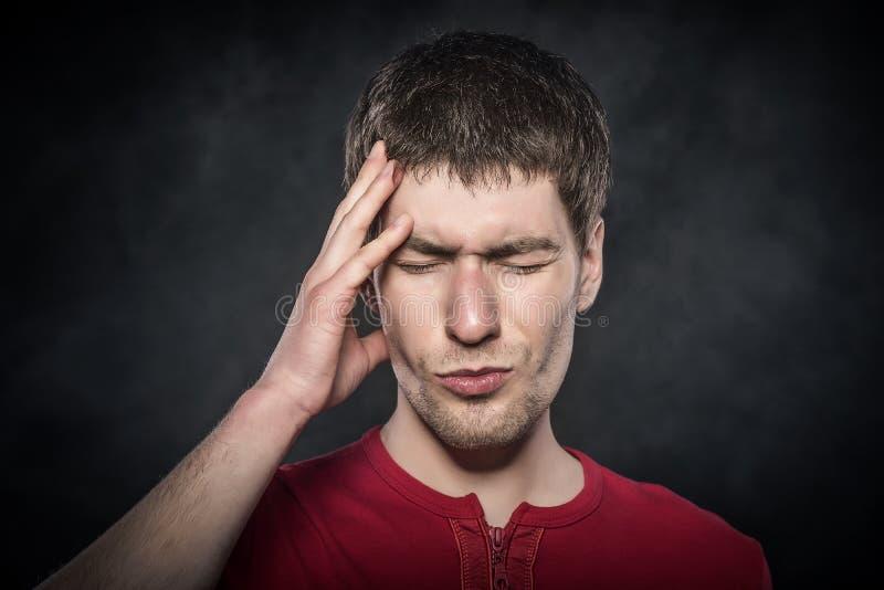 Man som känner en huvudvärk eller tänker intensely arkivfoto