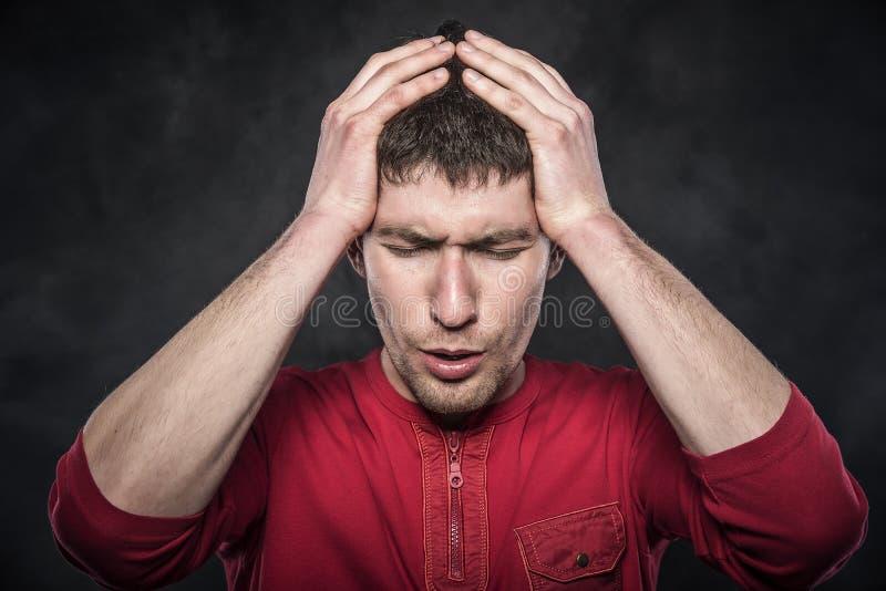 Man som känner en huvudvärk eller tänker intensely arkivfoton