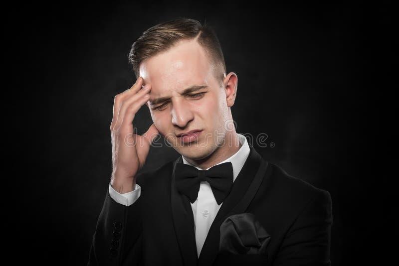 Man som känner en huvudvärk eller tänker intensely arkivbild