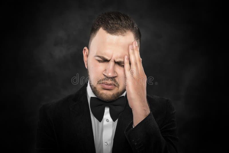 Man som känner en huvudvärk eller tänker intensely fotografering för bildbyråer