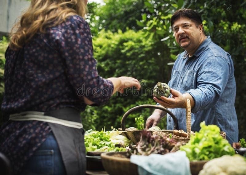 Man som köper den nya organiska grönsaken på marknaden arkivfoton
