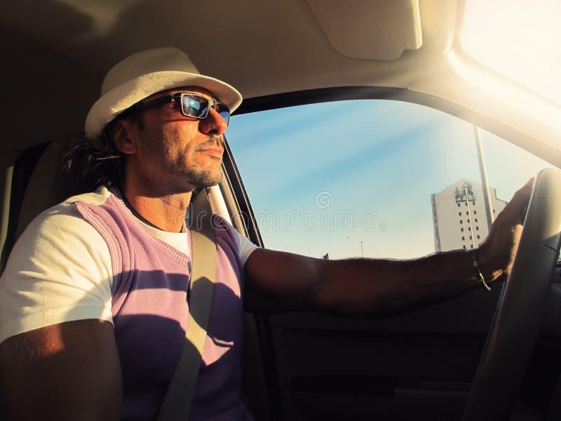 Man som kör bilen med hatten och solglasögon arkivbild