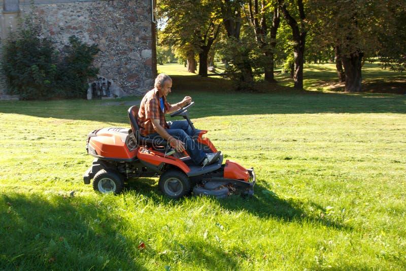Man som kör en röd gräsklippare (traktoren) royaltyfri bild