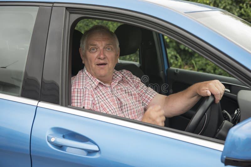Man som kör i hans bil som ser chockad fotografering för bildbyråer