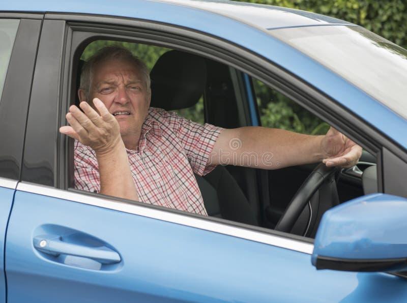 Man som kör i hans bil som ser ilsken royaltyfri foto