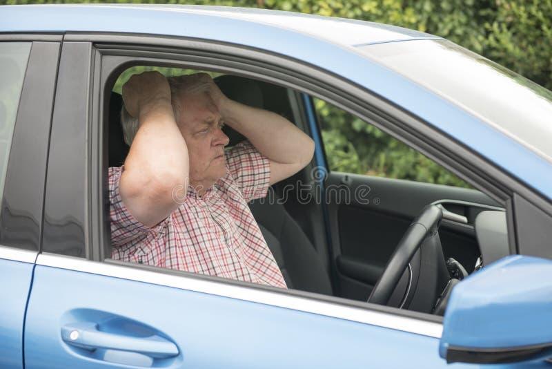 Man som kör i hans bil som ser ilsken royaltyfri bild